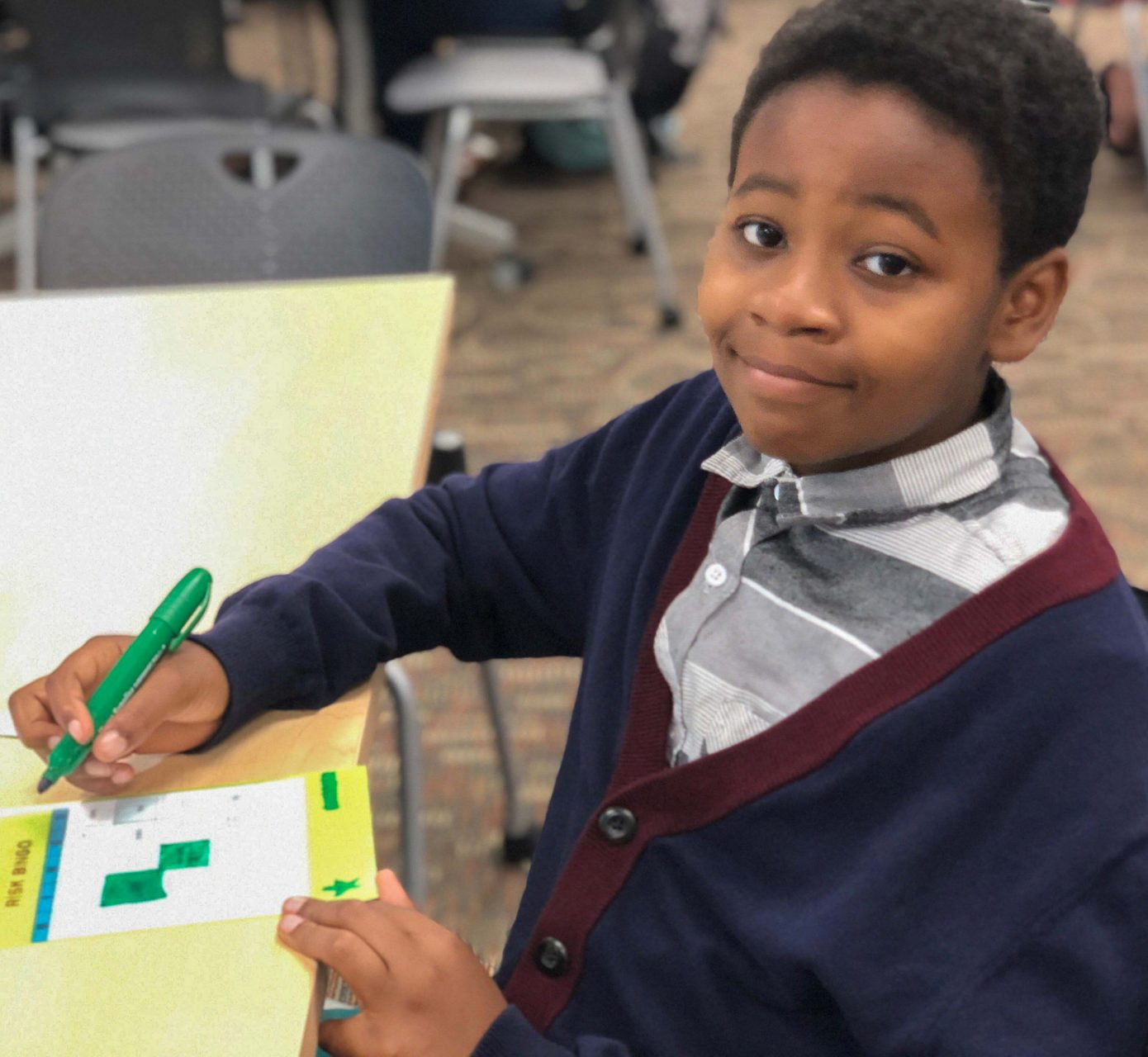 smiling boy in class writing