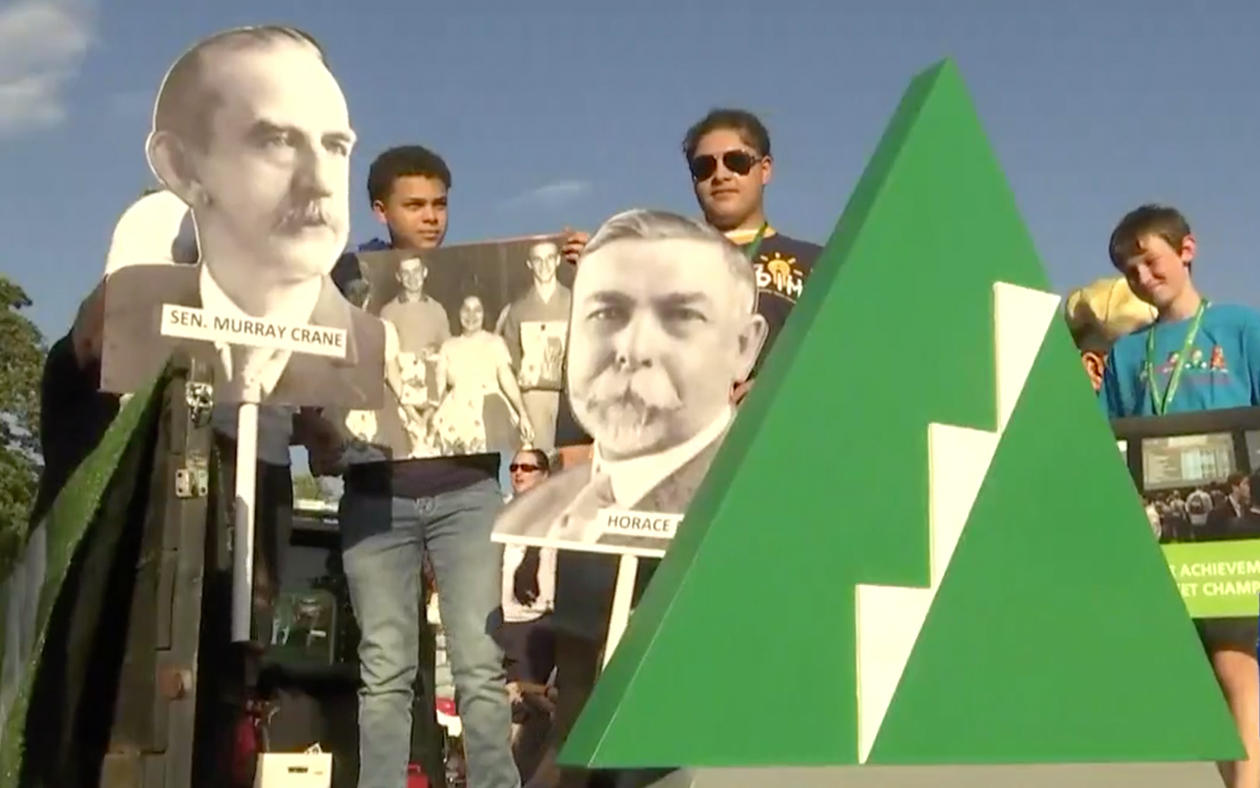 JA kids hold life size JA historial poster cutouts