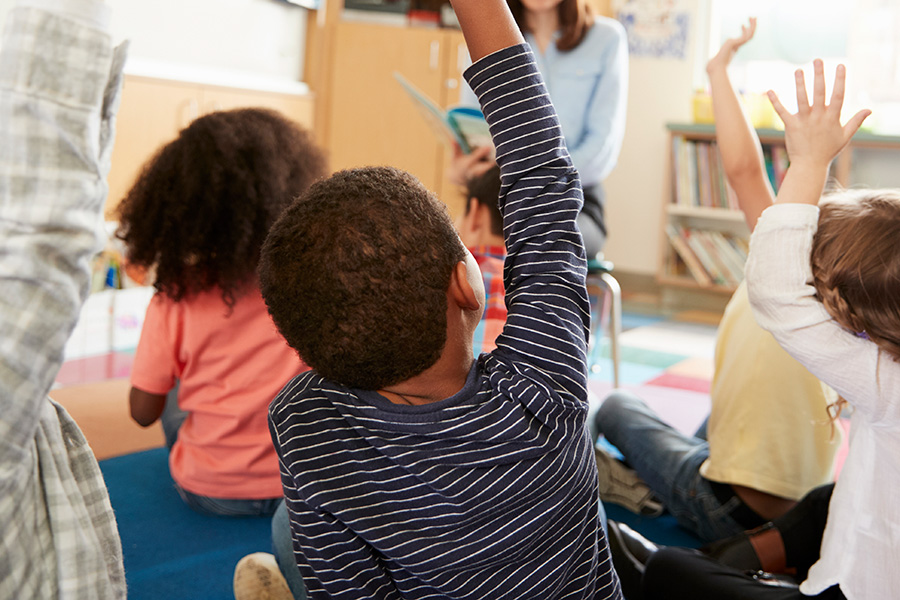 kids raising hands in class